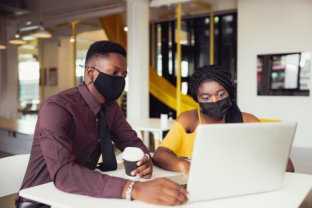 Studenti africani con gli amici che indossano la maschera seduti alla scrivania nella scuola moderna. protezione antivirus a scuola. messa a fuoco selettiva