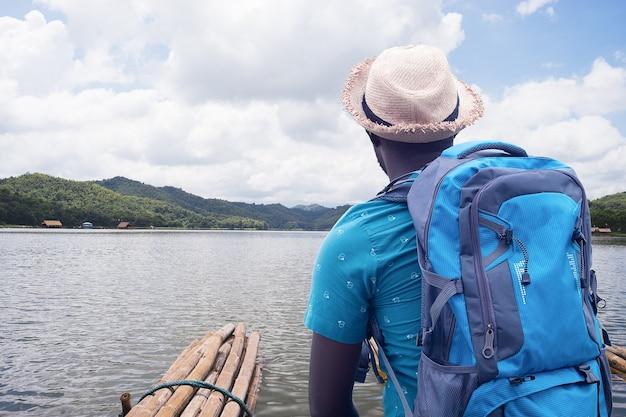 Uomo viaggiatore africano rafting nel fiume con lo zaino