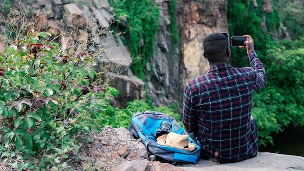 Viaggiatore africano che prende selfie dalla cima della montagna