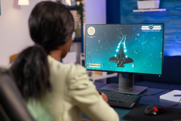 Videogiocatore africano che gioca di notte con il joystick. la donna competitiva del giocatore di cyber che esegue il torneo di videogiochi usa un joystick professionale.