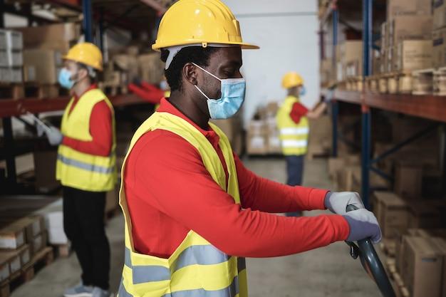 Magazziniere africano carico di scatole di consegna mentre indossa la maschera di sicurezza - focus sul viso
