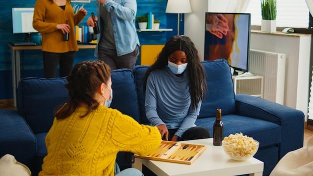 Donna africana in competizione con gli amici che giocano a backgammon indossando la maschera facciale mantenendo le distanze sociali durante la pandemia sociale con covid19 che beve birra in soggiorno. divertirsi con i giochi da tavolo in epidemia
