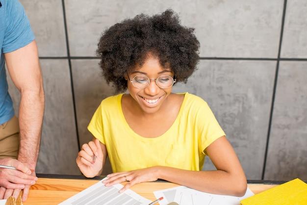 Donna africana vestita casualmente che studia o lavora con documenti al chiuso