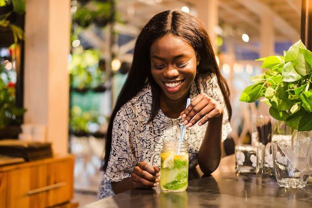 Donna africana che beve limonata con una cannuccia, in un ristorante