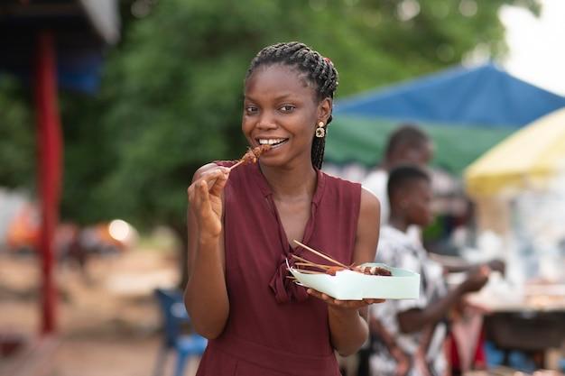 Donna africana che mangia cibo da strada