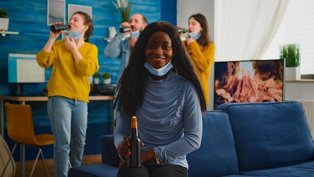 Donna africana che mantiene le distanze sociali indossando la maschera facciale mentre si incontra con gli amici per prevenire la diffusione del coronavirus con in mano una bottiglia di birra guardando la telecamera seduta sul divano, focolaio di covid 19
