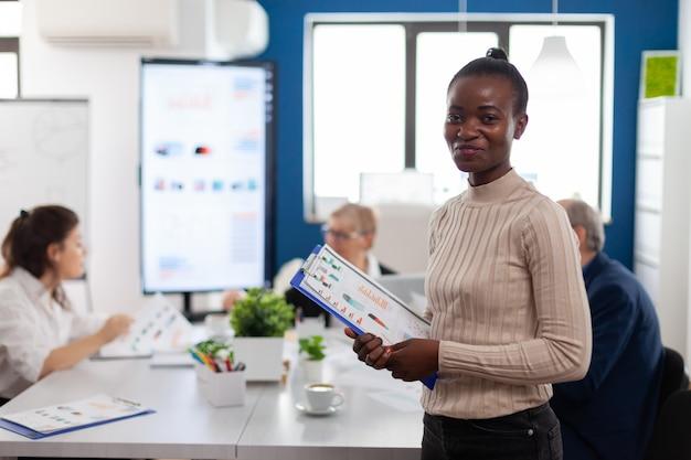 Donna africana manager che guarda l'obbiettivo sorridente, tenendo appunti, mentre diversi colleghi parlano in sottofondo. manager che lavora in attività finanziarie di avvio professionale, luogo di lavoro aziendale moderno