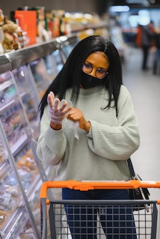 Donna africana che indossa una maschera medica usa e getta. fare la spesa al supermercato durante l'epidemia di pandemia di coronavirus. tempo di epidemia.