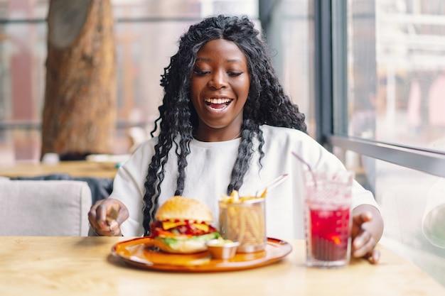 Donna africana con capelli afro che mangia un gustoso hamburger classico con patatine fritte. cheat meal.