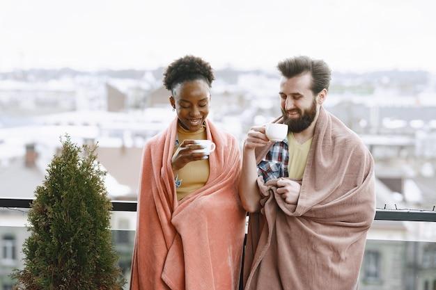 Donna africana con marito. ragazzo e ragazza in un plaid. amanti che bevono caffè sul balcone.