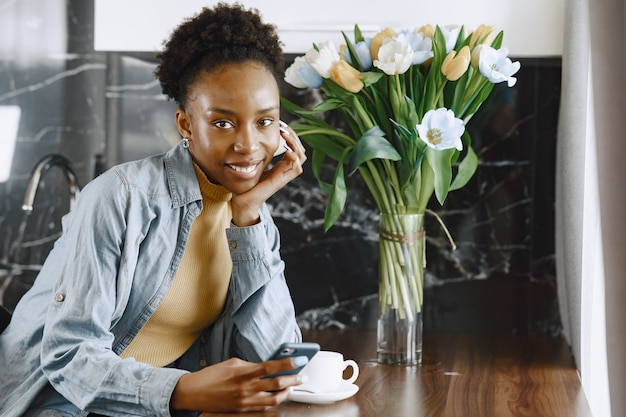 Donna africana con il telefono. ragazza con i capelli ricci. bouquet di fiori di tulipani.