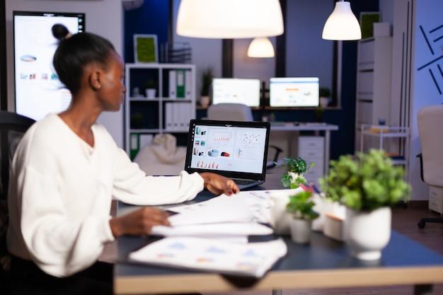 Donna africana che lavora a tarda notte guardando charst sul laptop