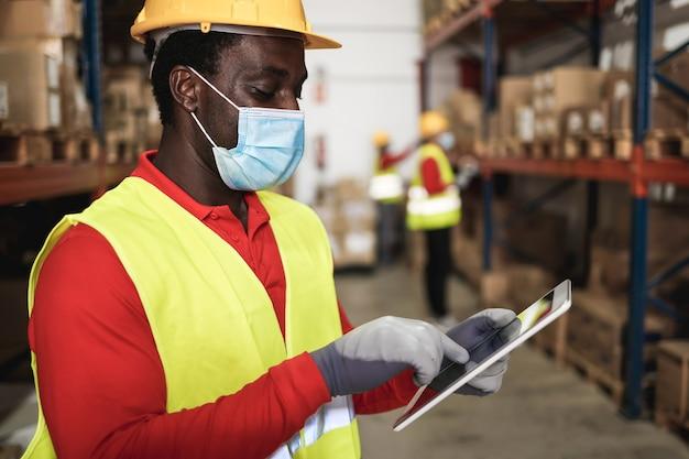 Uomo dell'operaio africano utilizzando tablet all'interno del magazzino mentre indossa la maschera di sicurezza - focus sul viso