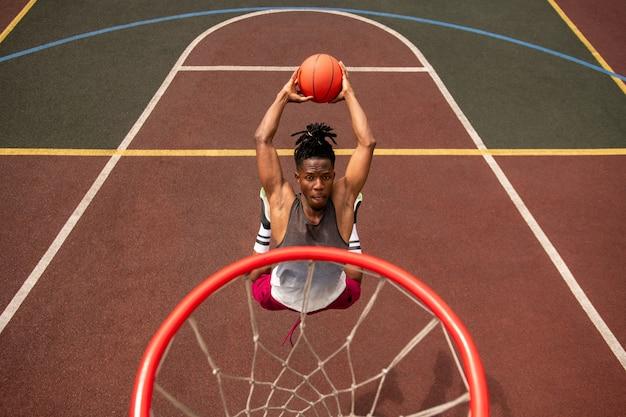 Giovane giocatore di pallacanestro africano che fa sforzo mentre salta e lancia la palla nel cestino durante l'allenamento