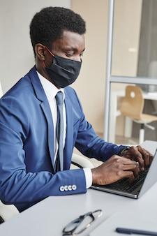 Giovane imprenditore africano in maschera protettiva seduto al suo posto di lavoro e digitando sul computer portatile che lavora durante la pandemia in ufficio