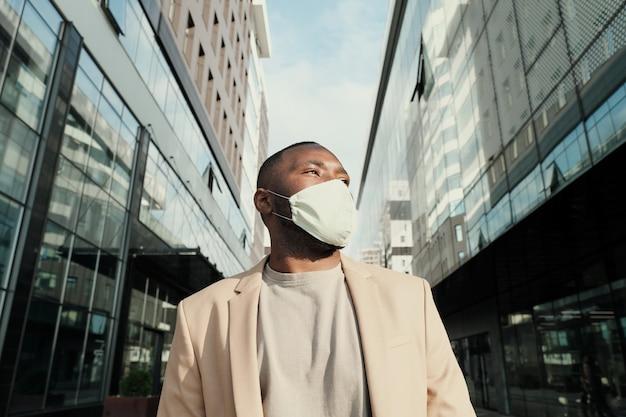 Giovane imprenditore africano in maschera protettiva in piedi in città con edifici moderni in background