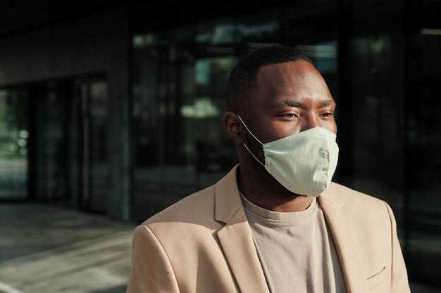 Giovane imprenditore africano in maschera protettiva in piedi all'aperto vicino all'edificio per uffici
