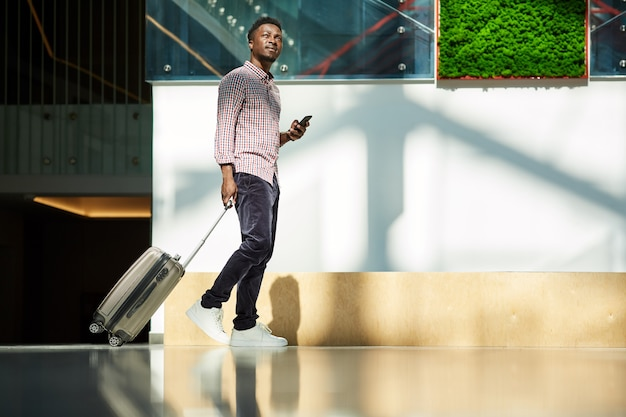 Il giovane uomo d'affari africano che cammina lungo il corridoio con i bagagli all'aeroporto ha un viaggio d'affari