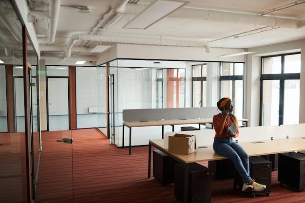 Giovane imprenditrice africana seduto al tavolo in ufficio vuoto e parlando al telefono cellulare