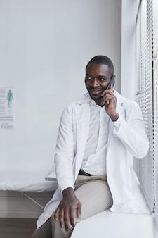 Giovane medico africano seduto vicino alla finestra e parlando al cellulare in ospedale