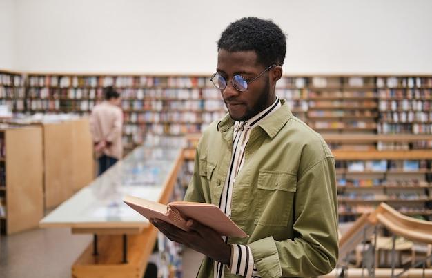 Giovane africano con gli occhiali che legge un libro mentre si trova in biblioteca