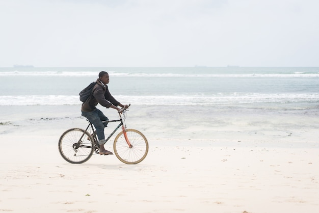 Giovane africano che guida la bici sulla spiaggia tropicale
