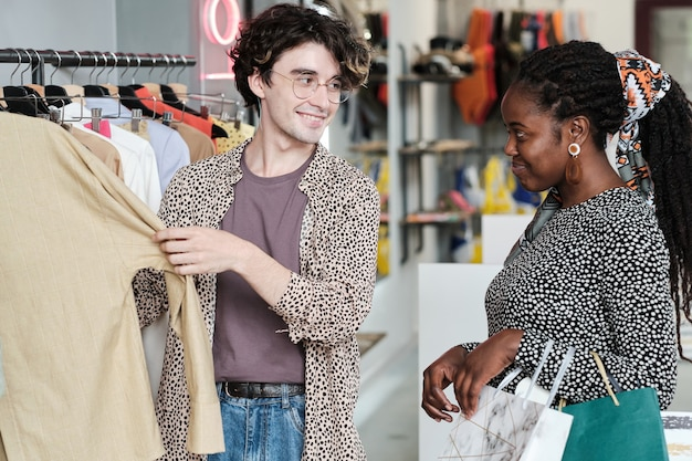 Giovane donna africana che sceglie un nuovo vestito per se stessa con l'aiuto della commessa nel centro commerciale