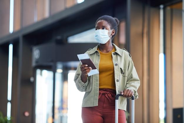 Giovane donna africana in maschera protettiva con bagagli che tengono i biglietti mentre si va lungo l'aeroporto