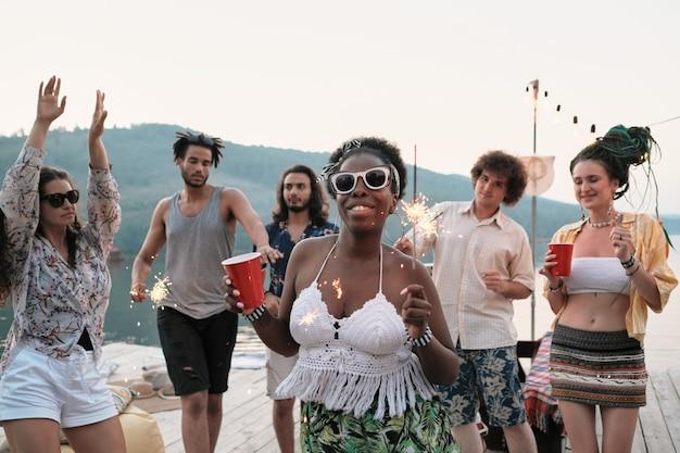 Giovane donna africana in occhiali da sole con un bicchiere di birra e stelle filanti sorride alla macchina fotografica mentre balla con i suoi amici alla festa all'aperto