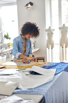 Il sarto da donna afroamericano disegna il motivo usando il gesso e la parte di cartone nel laboratorio di cucito