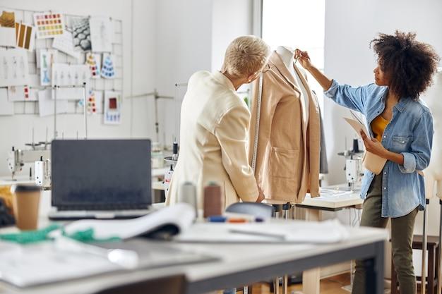 Signora afroamericana con colleghi maturi stilisti al lavoro su una giacca in officina