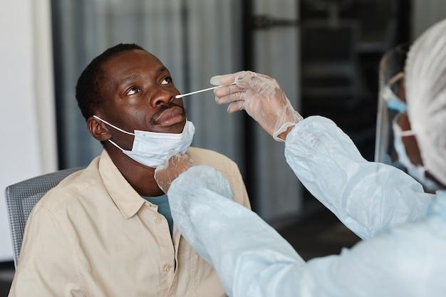Uomo afroamericano che visita il medico per il tampone nasale per ottenere il test del coronavirus di laboratorio