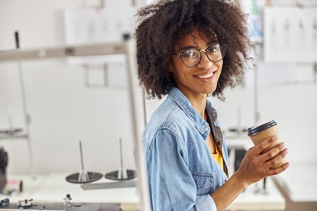 La sarta afroamericana con gli occhiali e l'orecchino nel naso tiene la tazza vicino alla macchina da cucire dentro