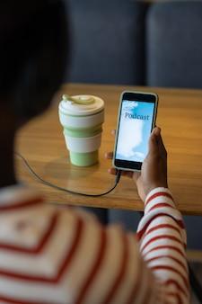 Donna afroamericana che ascolta un podcast dal suo smartphone