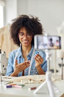 La donna afroamericana mostra una bobina di fili blu che gira un nuovo video per il blog in studio