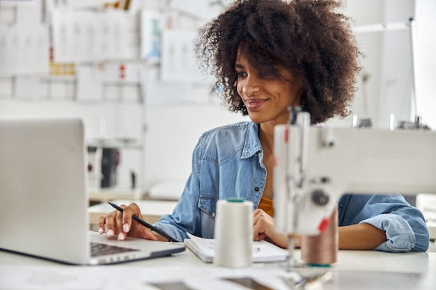 La donna afroamericana usa il computer portatile sul posto di lavoro con la macchina da cucire