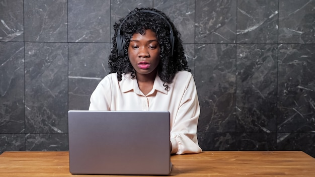Donna afroamericana con le cuffie in video chat da muro