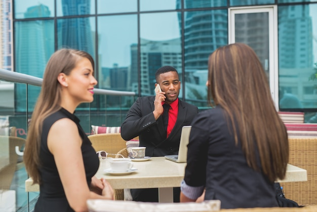 Uomo afroamericano di affari che parla sullo smart phone alla riunione del gruppo.