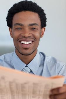 Uomo d'affari afroamericano con un giornale che sorride alla macchina fotografica