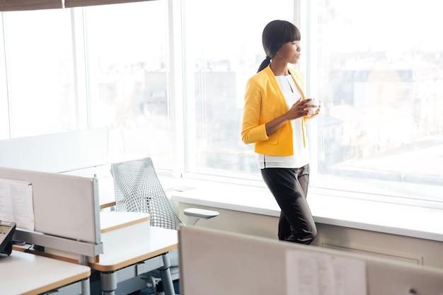 Donna d'affari afroamericana che beve caffè in ufficio