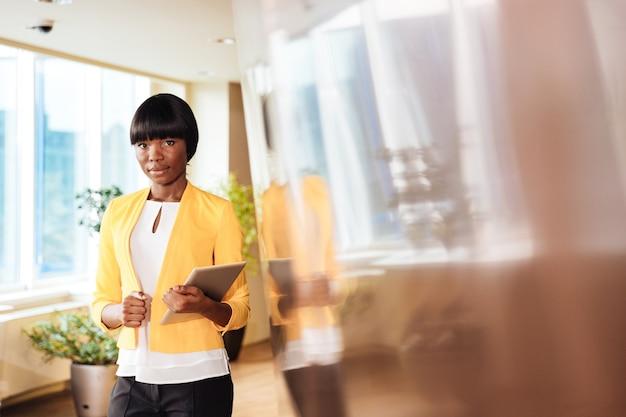 Donna di affari afroamericana che tiene il computer tablet in ufficio e guarda davanti