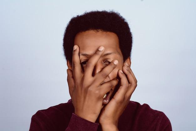 Afroamericano che copre il viso con la mano.