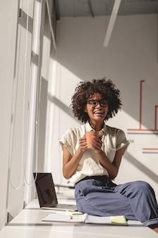 Manager femminile afroamericano con gli occhiali che si gode il caffè
