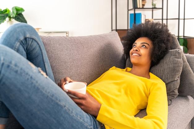 Ragazza afroamericana che beve una tazza di caffè e si rilassa a casa
