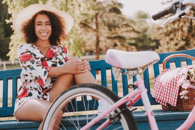 La ragazza afroamericana sta sedendosi sul parco e sta riposando nella foresta.