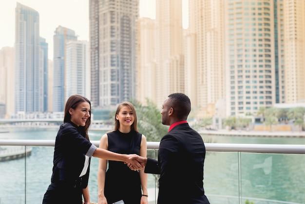 Stretta di mano afroamericana con intervista di lavoro attraente signora. incontro di uomini d'affari.