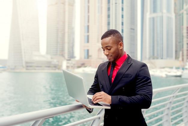 Sorridere di battitura a macchina del computer portatile di sguardo afroamericano. sfondo panoramico pieno di edifici alti.