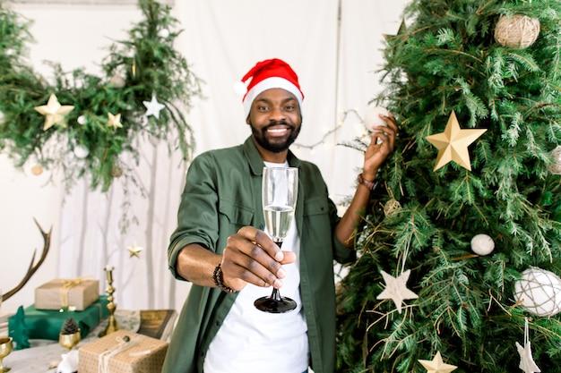 Uomo afroamericano che tiene champagne vicino all'albero di natale