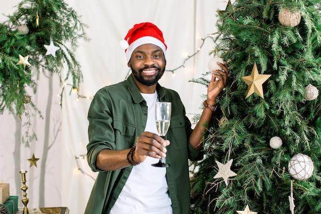 Uomo afroamericano che tiene vetro con champagne vicino all'albero di natale