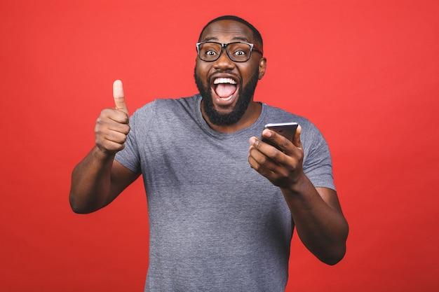 Uomo afroamericano che utilizza smartphone, felice con un grande sorriso che fa segno giusto, pollice in su con le dita